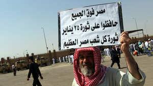 أحد المحتجين المناهضين لمبارك يحمل لافتة تطالب بحماية ثورة 25 يناير