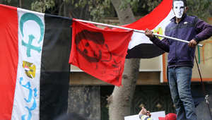 متظاهر يحمل العلم المصري مع علامتي الصليب المسيحي والهلال الإسلامي