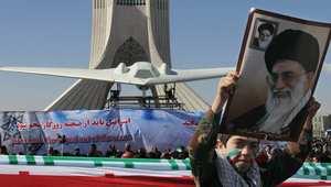 طفل إيراني يرفع صورة خامنئي أمام نموذج طائرة RQ-170  الأمريكية بدون طيارت التي تقول إيران إنها انتجت نسخا عنها