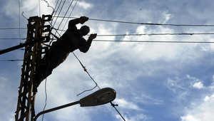 كهربائي يقوم بإصلاح أسلاك الكهرباء في حي باب التبانة في مدينة طرابلس شمال لبنان