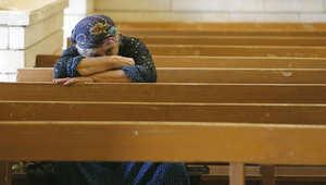 صورة ارشيفية لعراقية مسيحية تصلي بإحدى الكنائس