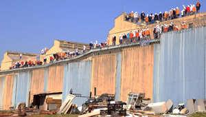 سجناء يقفون على سور السجن
