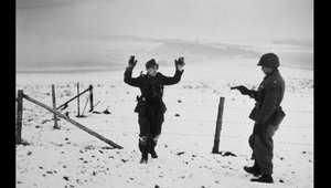جندي أمريكي يشهر مسدسه بوجه أسير حرب ألماني