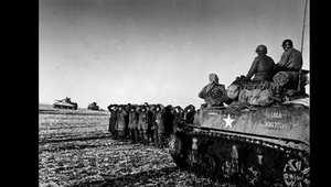 قوات أمريكية على متن دبابة يقف بجوارها أسرى حرب من الجنود الألمان