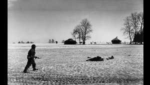 جندي أمريكي بأرض المعركة قد وظهرت بقربه جثة ضحية قتلت بالمواجهات
