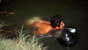 أرشيف- رجل يسبح ومعه حقيبة تحوي ملابسه الجافة في محاولة للتملص من الدوريات الأمريكية والعبور إلى البلاد بطريقة غير شرعية، 18 مارس/ آذار 2000