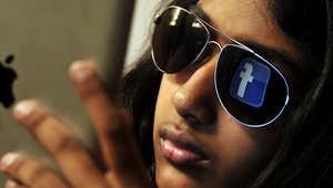 شعار فيسبوك ينعكس في النظارات الشمسية لشابة هندية