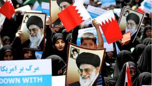 أرشيف - متظاهرون إيرانيون يرفعون صورة خامنئي وأعلام البحرين، بعد دعوة من السلطات للتظاهر بعد صلاة الجمعة احجاجا على ما اعتبرته طهران خطة لتوحيد البحرين مع السعودية 18 مايو/ أيار 2012