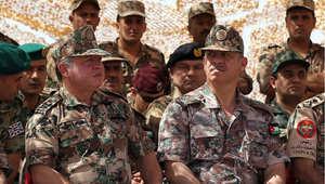 أرشيف- الملك عبدالله الثاني عاهل الأردن وإلى يساره شقيقه الأمير فيصل يتابعان مع ضباط من الجيش تمرينا عسكريا، 24 مايو / أيار 2012
