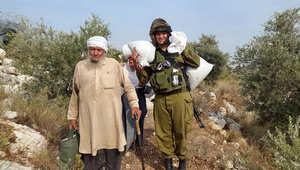 """المتحدث باسم الجيش الإسرائيلي ينشر صورة لجندي يساعد مسنا فلسطينيا.. ومدونون بين """"عيني ستدمع"""" و """"صوروني بسرعة الشوال ثقيل"""""""