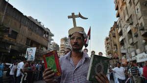 رجل مصري قبطي يحمل الكتاب المقدس والقرآن الكريم خلال مسيرة في القاهرة