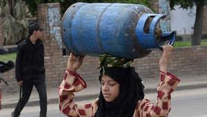 امرأة مصرية تحمل اسطوانة غاز فارغة ليتم تعبئتها في مستودع في القاهرة