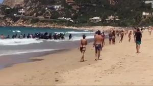 شاهد.. لحظة وصول قارب مهاجرين إلى شاطىء مزدحم بإسبانيا