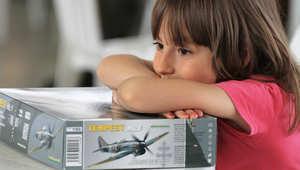 طفلة تستند على نموذج للعبة