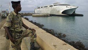 جندي جيبوتي ينظر إلى سفينة نقل أمريكية لقوات التدخل السريع في ميناء جيبوتي حيث يوجد للولايات المتحدة نحو 900 عسكري في معسكر ليمونير، 22 فبراير/ شباط 2003