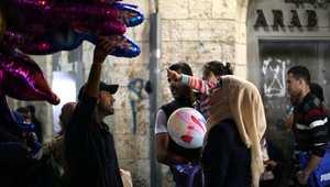 سيدة فلسطينية تنظر إلى مجموعة من البالونات يحملها أحد الباعة في مدينة رام الله بالضفة الغربية استعدادا لعيد الأضحى.