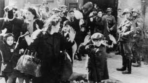 صورة من عام 1942 لأحد أحياء الغيتو اليهودية في وارسو حيث يقف الجنود الألمان بسلاحهم فيما يرفع اليهود أيديهم