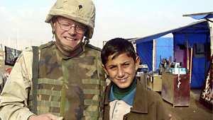 صورة أرشيفية لجندي أمريكي من كتيبة الدعم النفسي مع طفل عراقي في سنجار، في ديسمبر/ كانون الأول 2003