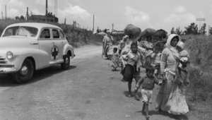 سيارة للصليب الأحمر تسير إلى جانب فلسطينيين خرجوا من القدس الغربية التي خضعت لسيطرة اليهود 1948