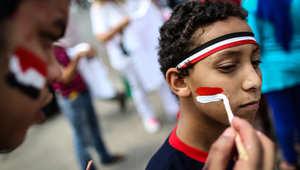 صبي مصري يرسم علم بلاده على وجهه أثناء مشاركته في احتفالات أمام القصر الرئاسي في القاهرة