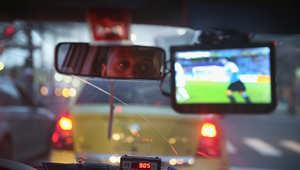 سائق يشاهد مباراة  كوستا ريكا وأوروغواي في سيارة الأجرة.
