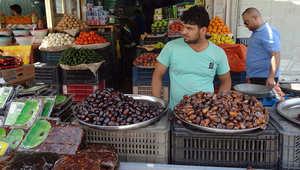 بائع عراقي يقف في محله بسوق في الكركوك.