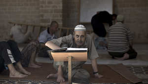 رجل فلسطيني يتلو  القرآن داخل مسجد العمري في أول يوم رمضان.