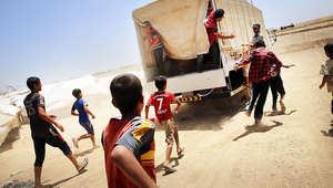 عراقيون يركضون خلف شاحنة تحمل مواد غذائية إلى مخيم للنازحين بالعراق.