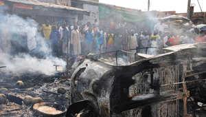 أرشيف - نيجيريون خالف مركبة محترقة جراء انفجار قنبلة في منطقة مزدحمة في سوق الاثنين في مايدوغوري، 1 يوليو/ تموز 2014