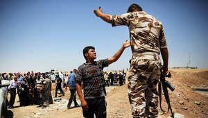 رجل عراقي يتجادل مع جندي كردي بعد فرار العراقيين من المعارك في الموصل وتلعفر