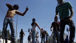 متظاهرون فلسطينيون يرمون الحجارة باتجاه الشرطة الاسرائيلية خلال اشتباكات في القدس