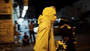 محتج ملثم يحمل قنبلتين حارقتين