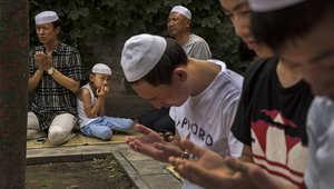 رجال وأطفال يقومون بالدعاء أمام مقابر الأئمة.