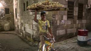 بائع خبز في مصر يركب دراجته ليوزع الخبر مع حلول موعد الإفطار في رمضان
