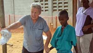 طبيبة من منظمة خيرية مسيحية تصطحب طفلا خارج الحجر الصحي الذي ادخل إليه بعد وفاة والدته بمرض ايبولا في العاصمة الليبيرية مينروفيا
