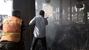 فلسطينيان يحاولان إخماد حريق في أحد المساجد بعد قصفه من قبل إسرائيل في غزة 29 يوليو/ تموز 2014