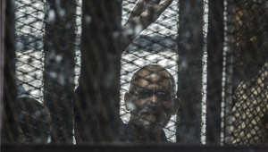 صورة للمرشد العام للإخوان المسلمين في مصر محمد عاكف في قفص الاتهام خلال إحدى جلسات محاكمته 3 أغسطس/ آب 2014