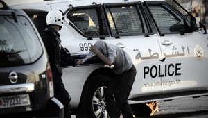 أرشيف- شرطي يلقي القبض على أحد المتظاهرين فيما تشتعل النار بإطارات سيارة الشرطة خلال احتجاجات بقرية سنابس، 3 ديسمبر/ كانون الأول 2013