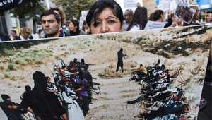 """متظاهرة تحمل صورة للمذابح التي ارتكبها """"داعش"""" ، خلال مظاهرة في برلين 17 أغسطس/ اب 2014"""