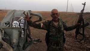 مقاتل كردي يتفحص بقايا عربة لداعش استهدفتها غارة أميركية شمال الموصل 18 أغسطس / آب 2014