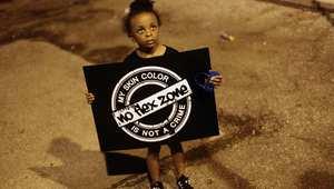 طفلة تحمل لافتة احتجاج في فيرغسون