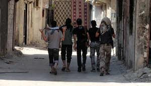 مقاتلون يحملون أسلحتهم إلى موقع على خط المواجهة في دمشق
