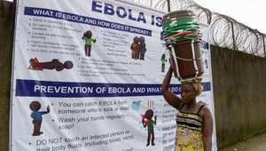 إمرأة في أحد شوارع مينروفيا تسير إلى جانب ملصق إرشادي عن الوقاية من إيبولا