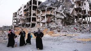 نساء فلسطينيات أمام بقايا مبنى محطم دمر خلال القتال بين حماس وإسرائيل