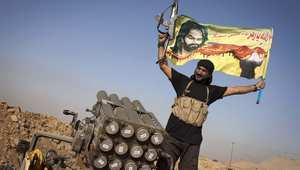 مقاتل عراقي من سرايا السلام التابعة للقائد الشيعي مقتدى الصدر يلوح براية عند راجمة صواريخ في مواجهة تنظيم داعش 31 أغسطس/ آب 2014