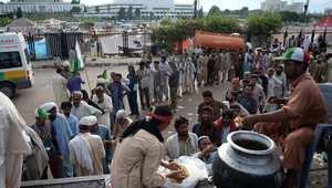إسلام أباد، باكستان -- باكستانيون من أنصار الشيخ طاهر القادري ومرشح الرئاسة عمران خان في ينتظمون في صف لتوزيع الطعام، خلال احتجاجهم أمام البرلمان للمطالبة باستقالة الحكومة