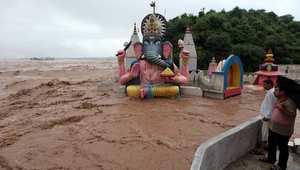هنديان ينظران من سطح إلى منسوب المياه المرتفع في نهر تواي ليغمر جزءا من معبد هندوسي في جامو 6 سبتمبر/ أيلول 2014