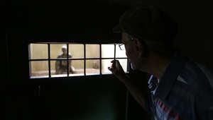 زائر ينظر الى داخل سجن من خلال شبك صغير في الباب