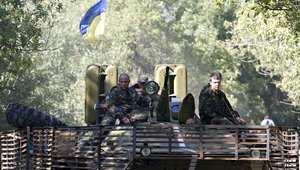 دونيتسك، أوكرانيا-- جنود اوكرانيون يرفعون في ناقلة جند مدرعة ترفع العلم الأوكراني 6 سبتمبر/ أيلول 2014