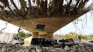 معسكر 27 ، ليبيا-- العلم الليبي يظهر تحت جسر مهدم جزئيا حيث أقامت الشرطة حاجزا على الطريق المؤدي إلى العاصمة طرابلس من جهة الغرب، حيث تتصارع مليشيات مسلحة للسيطرة على العاصمة، 9 سبتمبر 2014